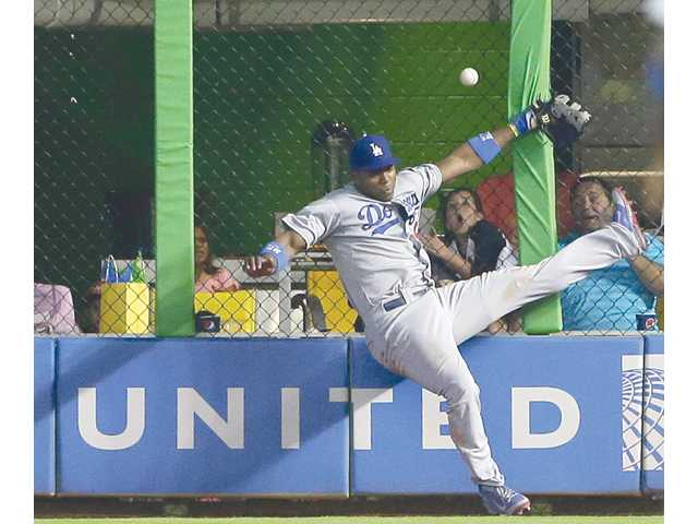 Los Angeles Dodgers right fielder Yasiel Puig is unable to catch a ball at the fence hit by Miami Marlin Jeff Baker, during the ninth inning on Sunday in Miami.