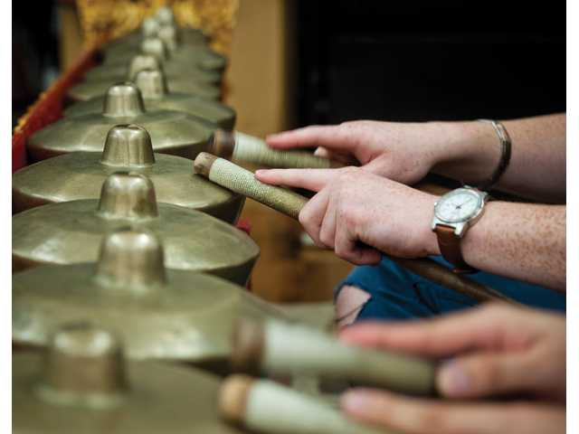 CalArts students use panggul (gong mallets) to drum on a reong, a type of Balinese horizontal gong used to provide the principle melody of a song.