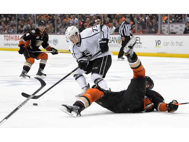 Anaheim Ducks right wing Corey Perry, right, falls as Los Angeles Kings center Tyler Toffoli, center, takes the puck while Ducks defenseman Cam Fowler looks on Monday in Anaheim.