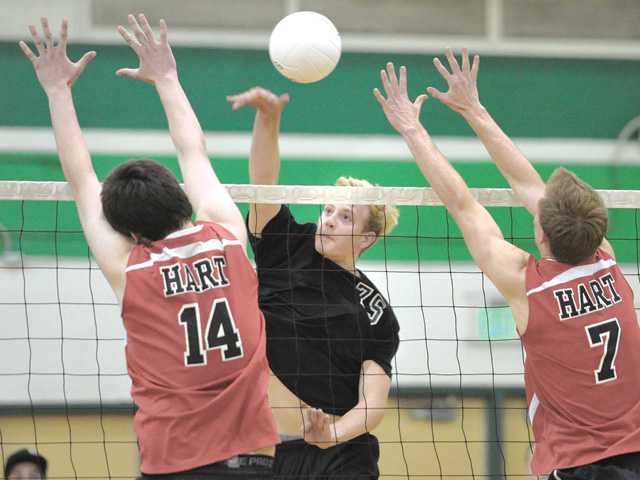 Canyon's Jake DeYoung hits the ball against Hart defenders Justin Fortner (14) and Luke Maly (7) at Canyon High on Tuesday.