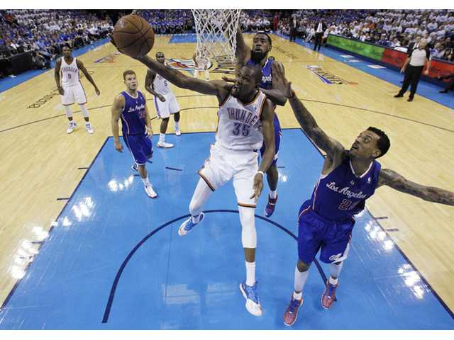 Oklahoma City Thunder forward Kevin Durant (35) shoots between Los Angeles Clippers center DeAndre Jordan and forward Matt Barnes (22) in Oklahoma City on Wednesday.