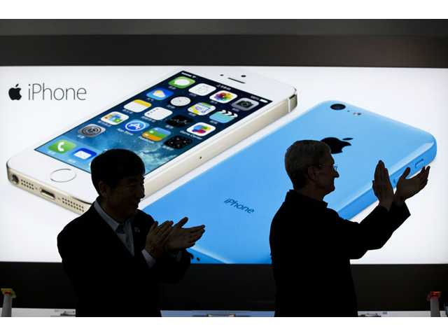 In this Jan. 17 file photo, Apple CEO Tim Cook, right, and China Mobile's chairman Xi Guohua are silhouetted against a screen showing iPhone products as they applaud during a promotional event that marks the opening day of sales of China Mobile's 4G iPhone 5s and iPhone 5c at a shop of the world's largest mobile phone operator in Beijing, China.