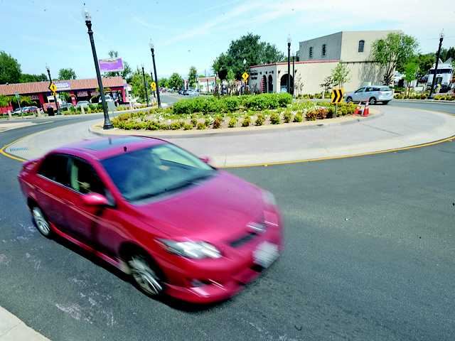 Cars travel around the roundabout at the end of Main Street in Newhall on Friday.
