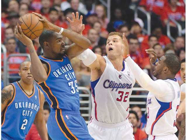 Oklahoma City Thunder forward Kevin Durant, left, passes the ball as Los Angeles Clippers forward Blake Griffin (32) defends on Friday in Los Angeles.