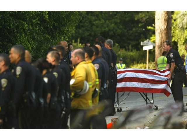 A police officer pulls the gurney carrying the body of an off-duty police officer, who was killed in an accident with a cement truck, in Beverly Hills on Friday.