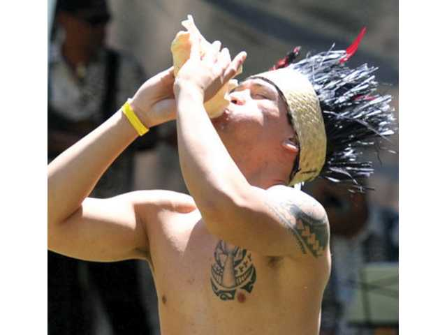 Niko Alefosio sounds a conch shell during a dance at the first Santa Clarita Pacific Islander Festival at William S. Hart Park in Newhall on Saturday.