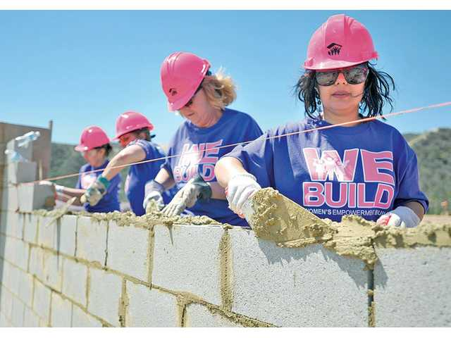 Wrangah Dargahr applies mortar to cement blocks to build a wall at the WE Build event for Habitat for Humanity of the San Fernando and Santa Clarita Valleys on May 10.