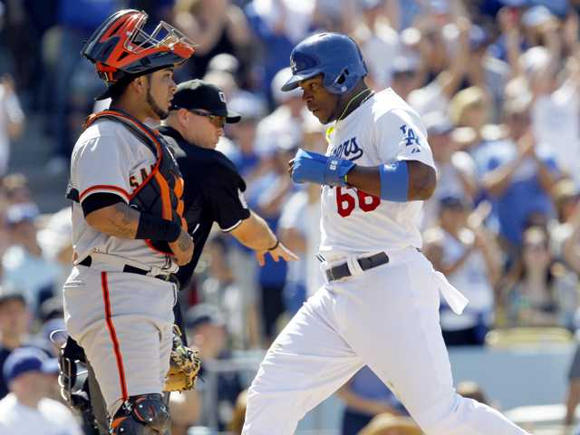 Los Angeles Dodgers' Yasiel Puig (66) scores as San Francisco catcher Hector Sanchez looks on after during Saturday's game in Los Angeles.