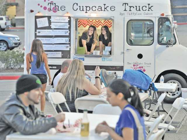 Tiffany and Marilyn Ramos welcome customers while in The Cupcake Truck, one of the number of food trucks serving meals in the parking lot across from the Walmart on Carl Boyer Drivein Santa Clarita.
