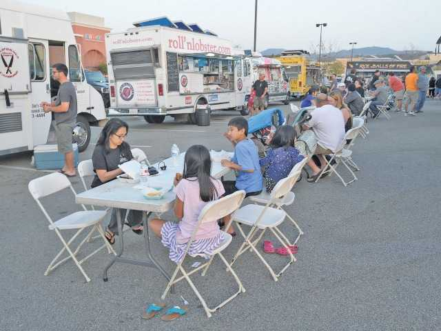 Families enjoy their dinner from the food trucks.