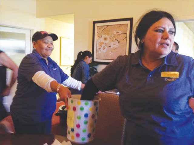 Luz Mardighomi, right, reaches into the raffle bucket for a ticket with the help of Denise Tunson during the Mother's Day Raffle at Eternal Valley Memorial Park & Mortuary in Newhall on Sunday. Signal photo by Jim Holt.