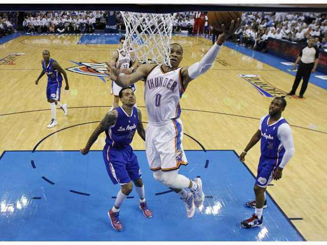 Oklahoma City Thunder guard Russell Westbrook (0) shoots between Los Angeles Clippers forward Matt Barnes (22) and guard Chris Paul (3) in Oklahoma City on Tuesday.