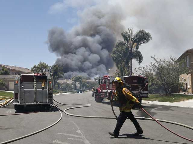 A fireman drags a hose as smoke rises from a nearby wildfire Wednesday, May 14, 2014, in Carlsbad, Calif. Carlsbad city officials said mandatory evacuations were in progress Wednesday, and more than 11,000 notices were sent to homes and businesses.