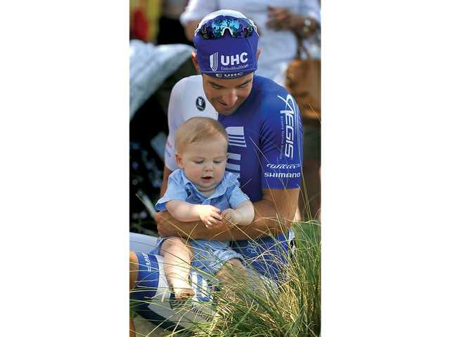 Christopher Jones, cyclist for UnitedHealthcare Pro Cycling Team, holds his 6-month-old son, Tennyson, before the start of the Amgen Tour of California Stage 6 in Newhall on Friday. Signal photo by Katharine Lotze