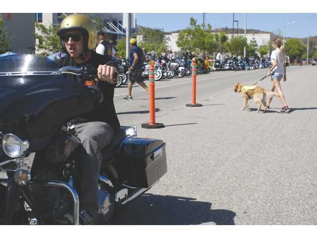 A motorcyclist drives by with a guide dog in the background at the Guide Dogs of America Rides for Guides event in Santa Clarita on Sunday.