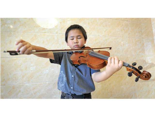 Jacob Zheng, 9, poses with his viola at Ocean Seafood Buffet. Zheng often plays for customers at the restaurant.