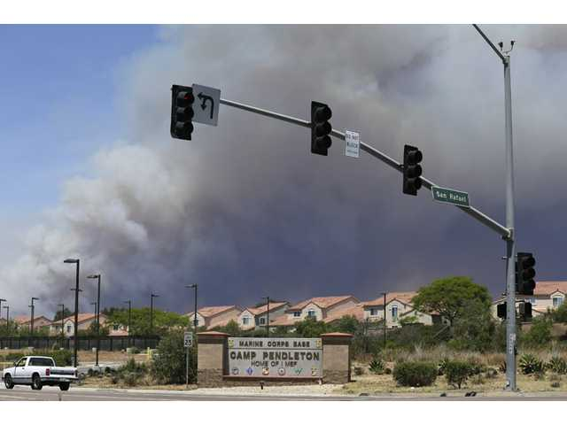 Smoke plumes rise behind the Marine Corps Camp Pendleton entrance on Friday in Oceanside.