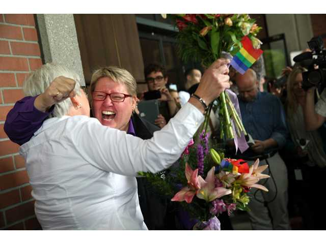 Deanna Geiger, left, and Janine Nelson, her partner of 32 years, react to news that they can get their Oregon marriage license Monday in Portland, Ore., following a federal judge's ruling the ban of same-sex marriage unconstitutional.