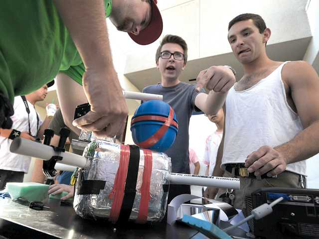 West Ranch High classmates (from left to right) Maxwell Schwarz, Hunter Lindorg and Daniel Tikhomirov attach cameras to a balloon on Friday at the school with the intent of collecting cosmic dust.