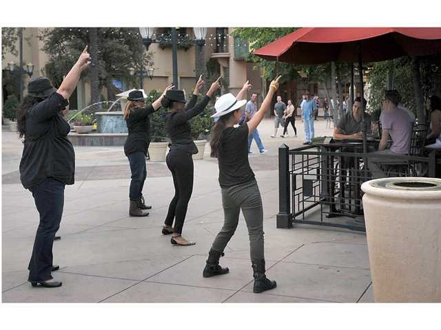 Members of the Dance Mob Nation of Los Angeles dance for a surprise marriage proposal for Art Sequeira and Chris Turpin outside the Salt Creek Grille on Wednesday. Signal photo by Katharine Lotze.