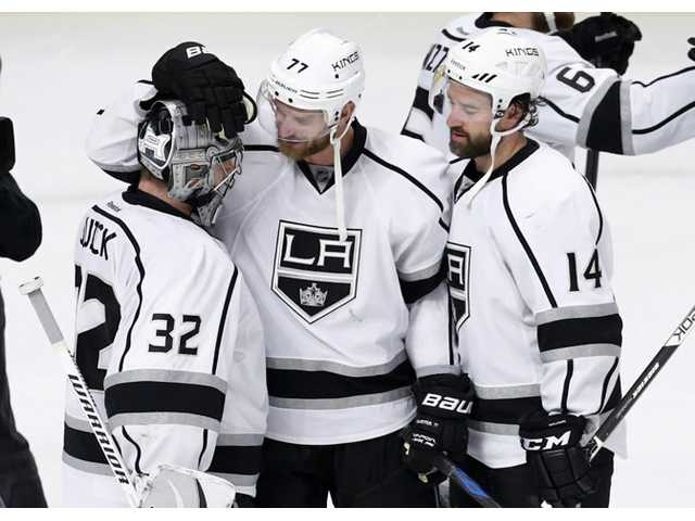 Los Angeles Kings center Jeff Carter (77) and Justin Williams (14) celebrate the Kings' 6-2 win over the Chicago Blackhawks with goalie Jonathan Quick on Wednesday in Chicago.