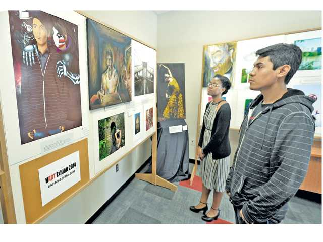 Hart High seniors Kayla Johnson, center, and Steven Zavalla examine the artwork on display in the main lobby of the Hart Exhibit 2014 held at Hart High Schooll on Friday.