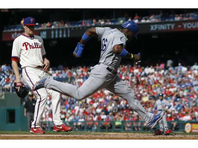 Los Angeles' Yasiel Puig, right, scores past Philadelphia Phillies relief pitcher Jacob Diekman on a passed ball during the sixth inning of Saturday's game in Philadelphia.