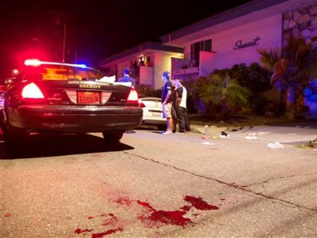 Police investigate the scene of a drive-by shooting that left seven people dead, including the attacker, and others wounded on Friday, May 23, 2014, in Isla Vista, Calif.