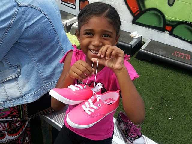 A recipient of The Shoe Crew's donated sneakers smiles.