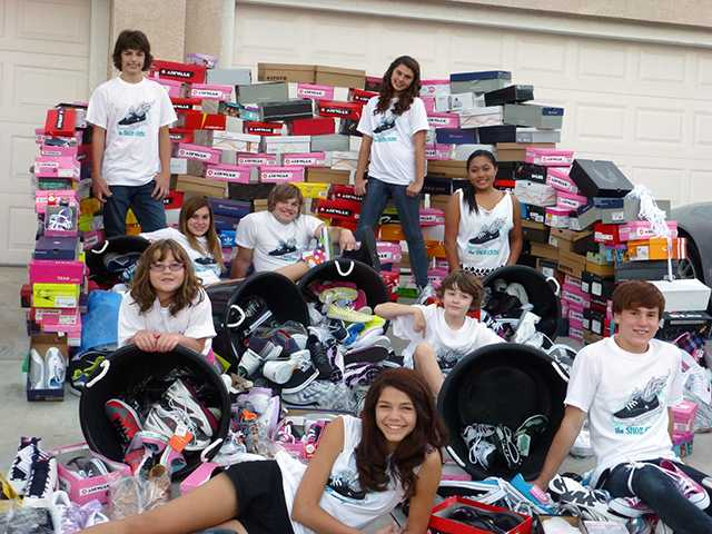 Members of The Shoe Crew pose with donations they've raised.