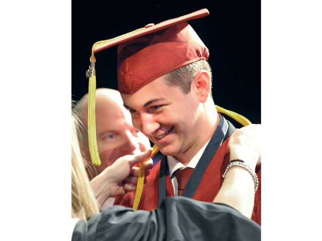 Trinity Classical Academy graduating senior Grant Doohen smiles as he receives his diploma during the Trinity Classical Academy graduation ceremony held at the school in Valencia on Saturday.