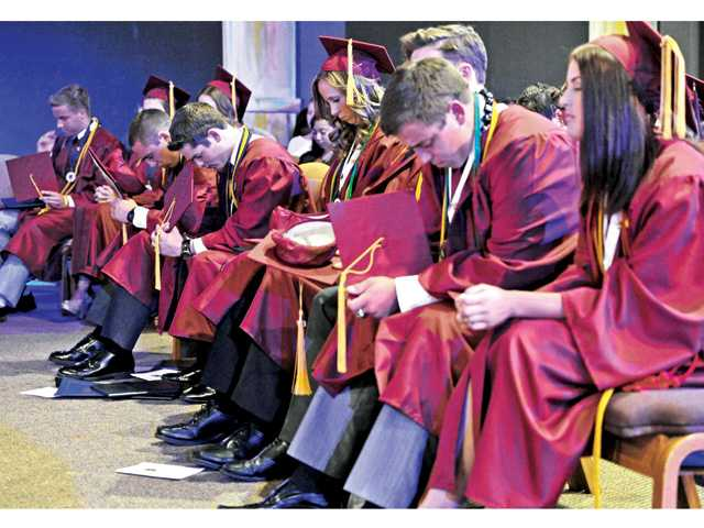 Members of the Trinity Classical Academy graduating class bow their heads during the graduation ceremony for the 2014 Senior Class at the Trinity Classical Academy graduation ceremony held in Valencia on Saturday.