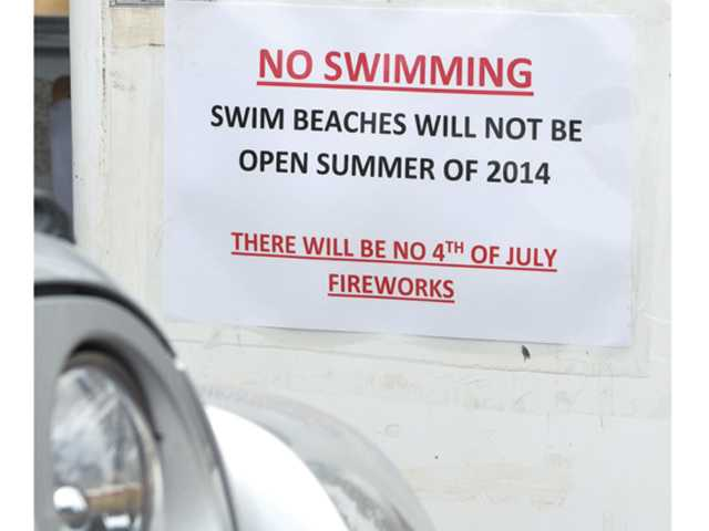 Signs posted at the entrance to Castaic Lake State Recreation Area notify visitors that the swimming beaches are closed for the summer due to low water levels and that there will no 4th of July fireworks at the lake this year. Signal photo by Dan Watson.