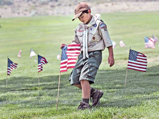 Boy Scout Jake Tustin, 11, of Troop 303 of Canyon Country joins 300 Boy Scouts, Cub Scouts, Girl Scouts and Brownies on Saturday as they plant an estimated 5,000 American flags on the graves of people with military service in honor of Memorial Day at Eternal Valley Memorial Park & Mortuary in Newhall. Signal photo by Dan Watson.