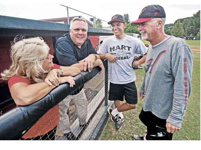 From left, Ilona, Jeff and Nick Valaika chat with Hart High baseball coach Jim Ozella before a practice at Hart High School on Thursday.