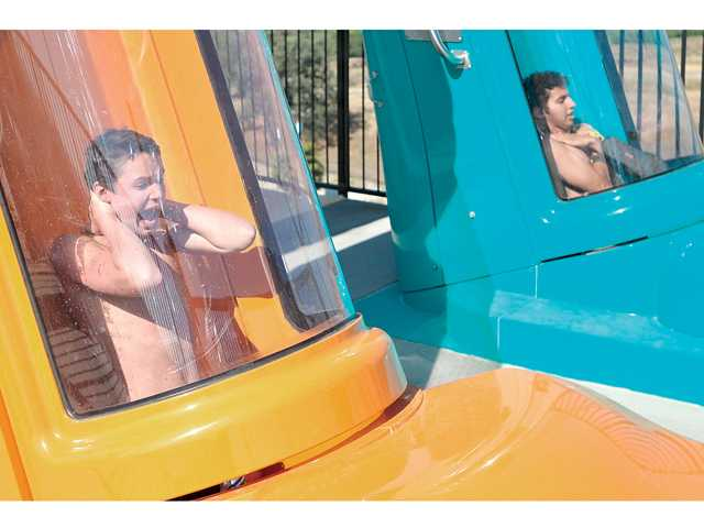 Some visibly nervous riders get their first taste of Six Flags Hurricane Harbor's new ride, Bonzai Pipelines, as the capsule bottom drops out from under their feet during the slide's opening day on Monday. Signal photo by Katharine Lotze.