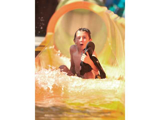 Jonathan Hicks, 10, emerges from one of the two new water slides that make up the Bonzai Pipelines.Signal photo by Katharine Lotze.