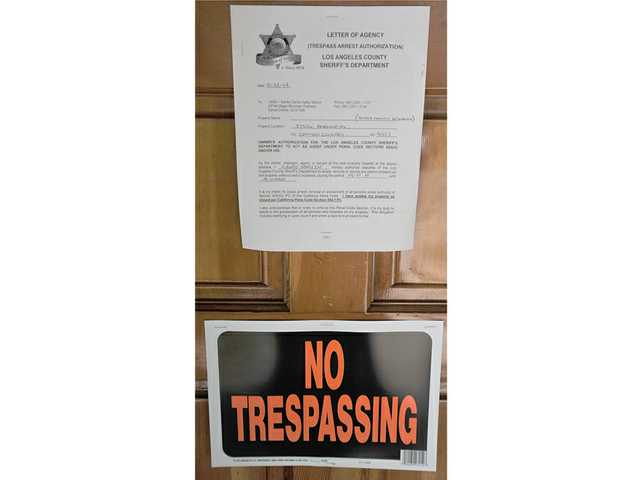 A letter warning sheriff's deputies may arrest anyone trespassing in a Canyon Country home was posted on the door after the house was boarded up by city, county and law-enforcement officials. Signal photo by Katharine Lotze