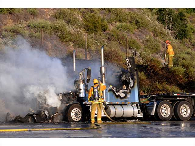 Firefighters mop up after a big rig fire spread to the brush off Highway 14 south of Newhall Tuesday evening, burning about a quarter acre. Photo by Rick McClure.