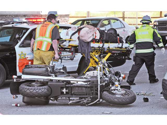An injured motorcyclist is carried to a waiting ambulance after a collision on Soledad Canyon Road Wednesday involving a Harley-Davidson, an SUV and a Honda. Only the motorcyclist was injured, officials said. Signal photo by Dan Watson