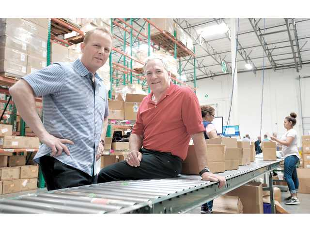Jay Catlin, president and managing partner of AMS Fulfillment (left), and Ken Wiseman, CEO in one of their warehouses. Photo by Katharine Lotze.