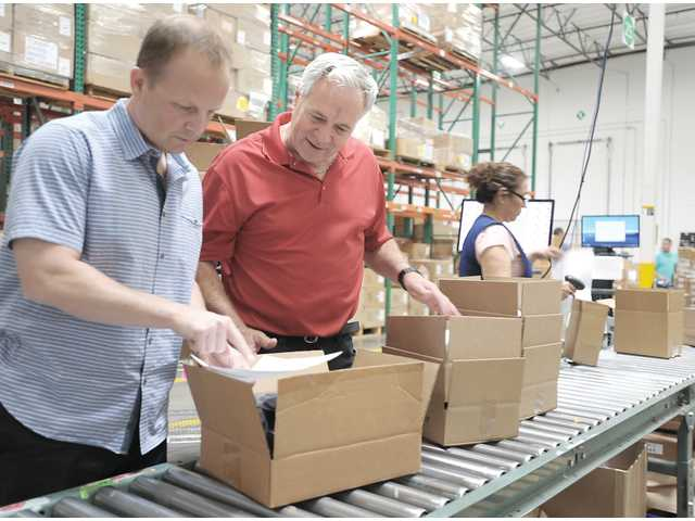 Jay Catlin, president and managing partner of AMS Fulfillment, left, and Ken Wiseman, CEO, check merchandise for a SpaceX order in one of their warehouses. Photo by Katharine Lotze.