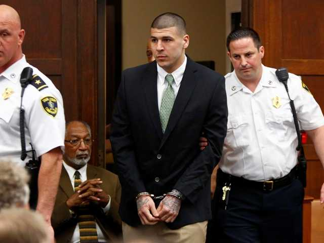 Former New England Patriots tight end Aaron Hernandez is led into the courtroom to be arraigned on homicide charges at Suffolk Superior Court in Boston, Wednesday, May 28, 2014.