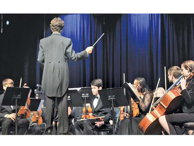 "Eighth-grader Robby Good conducts Placerita Junior High's orchestra as they play his ""Legend of Zelda Medley"" at Hart High School. Signal photo by Katharine Lotze."