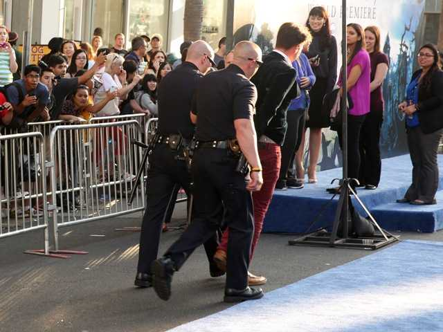 Journalist Vitalii Sediuk is walked off carpet in handcuffs after allegedly attacking Brad Pitt