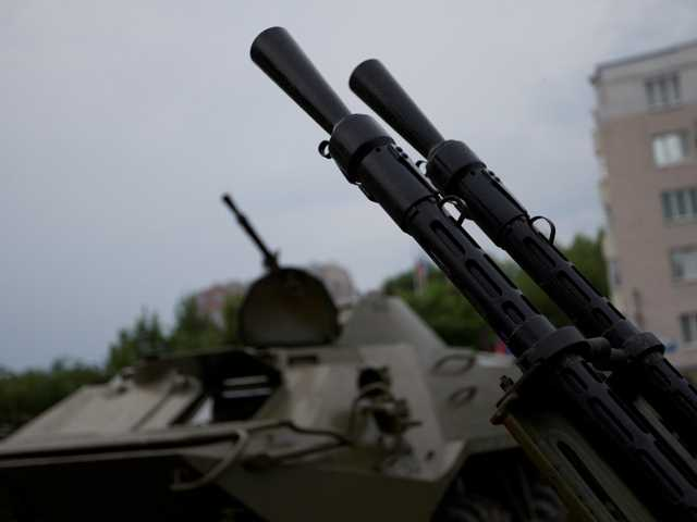 Barrels of an anti-aircraft gun and an APC are seen outside the administration building in Donetsk, Ukraine