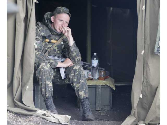 A Ukrainian soldier take a rest at a checkpoint outside Slovyansk, Ukraine, Friday, May 30.