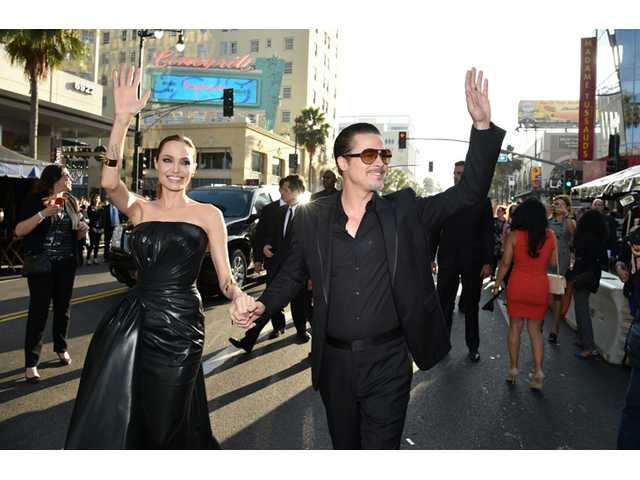 "Angelina Jolie, left, and Brad Pitt arrive at the world premiere of ""Maleficent"" at the El Capitan Theatre."