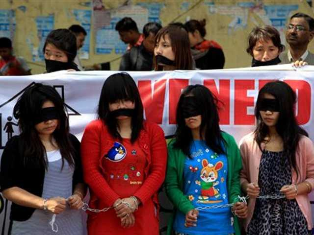 In this March 8, 2014 file photo, Myanmarese refugee women handcuff, blindfold and cover their mouths with black cloths during a protest on International Women's Day in New Delhi.