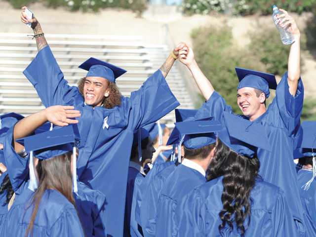 C.J. Sloan, left, and Tyler Pacheco celebrate on their chairs as they look to the stands during the Bowman High School graduation held at College of the Canyons in Valencia on Saturday.
